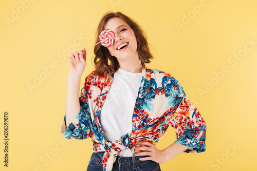 Fototapety, obrazy: Portrait of pretty cheerful lady in colorful shirt standing and covering her face with lollipop candy while happily looking in camera on over pink background