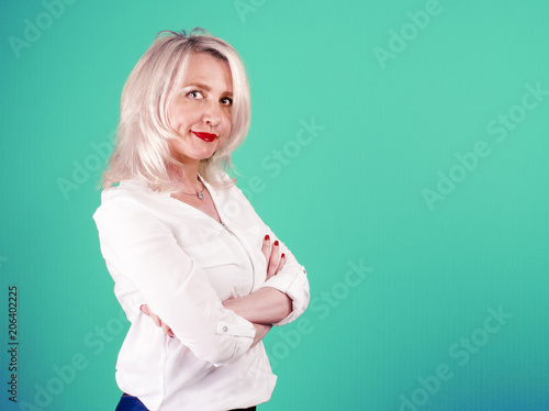 Valokuva  A mature woman in a white blouse crossed her arms over her chest against a bright background