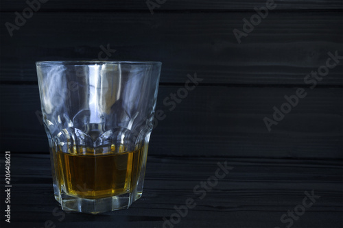 Fotobehang Alcohol a glass with alcohol on a dark, woody background