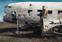 Man Sitting On Old Destroyed Airplane