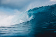 Breaking barrel wave in ocean. Blue wave and sky with clouds in Bali