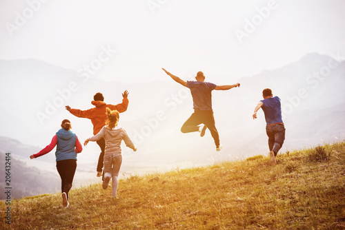 Happy friends runs and jumps outdoors