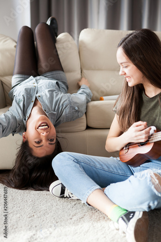 Fototapeta Happiness and friendship. Two girls in the bedroom having fun and one is playing at a small guitar obraz na płótnie