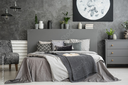 Fototapety, obrazy: Moon poster on concrete wall above bed with bedhead in grey bedroom interior. Real photo