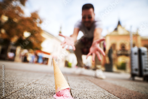Fotografija  Close up picture of an icecream on street dropped by a mourning man