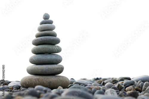 Fotografia  a pyramid of stones on a pebble beach isolated on a white background