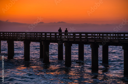 Poster Fantastique Paysage Silhouettes of two people walking on wooden pier at the ocean during amazing sunset, orange and purple sky