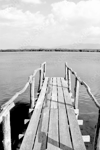 Deurstickers Poort Old wooden bridge or pier to the sea in black and white, Thailand.