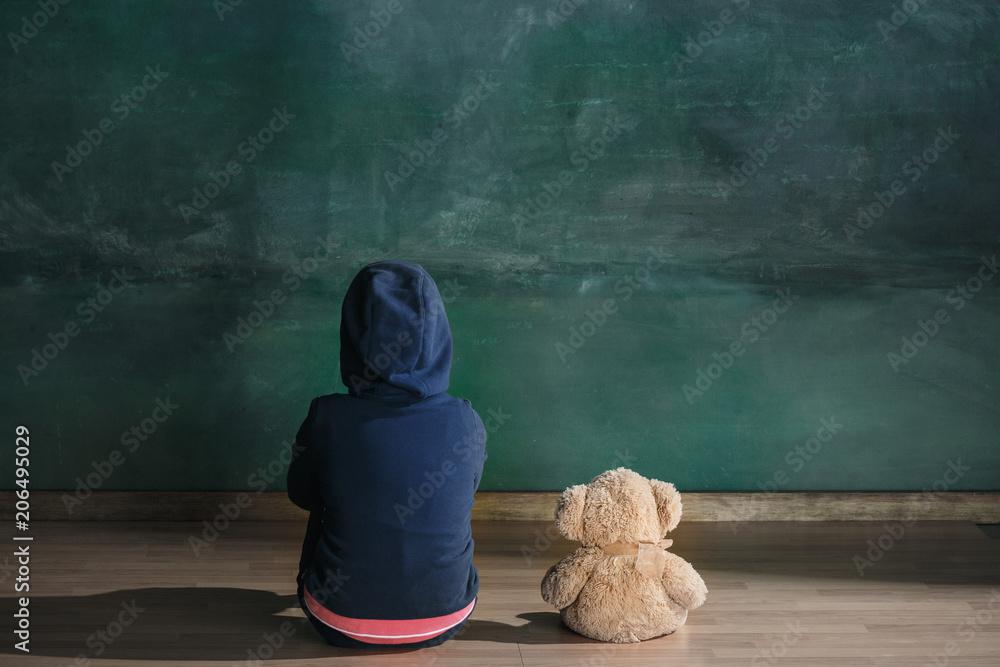 Fototapeta Little girl with teddy bear sitting on floor in empty room. Autism concept - obraz na płótnie