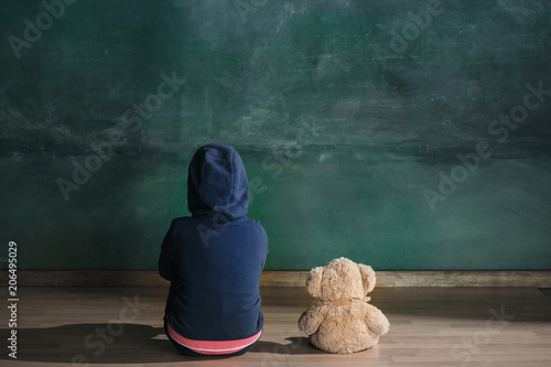 Fotografía  Little girl with teddy bear sitting on floor in empty room
