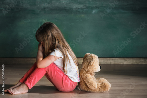 little-girl-with-teddy-bear-sitting-on-floor-in-empty-room-autism-concept
