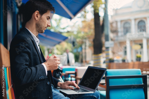Valokuva  Young handsome man enjoy coffee working on laptop