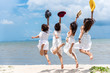 Group of four women in white dress and wearing hat jumping along the beach with blue sky background. Summer and vacation conceept.