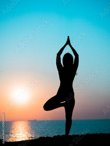 Fototapeta Young slim girl practicing yoga on mountain against ocean or sea at sunrise time. Silhouette of woman in rays of awesome sunset. obraz na płótnie