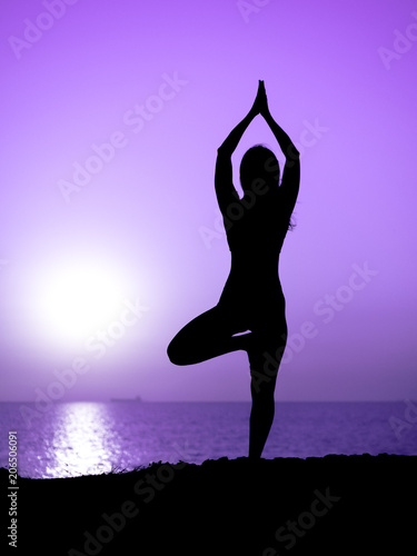 Fotobehang Draw Young slim girl practicing yoga on mountain against ocean or sea at sunrise time. Silhouette of woman in violet rays of awesome sunset.