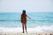 A child in a cap on the seashore. A little girl catches waves