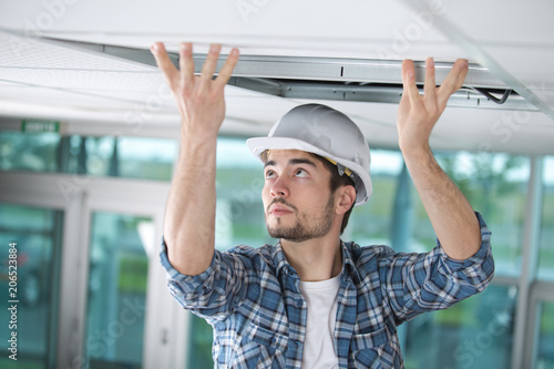 Photo man in builder uniform hand up installing suspended ceiling
