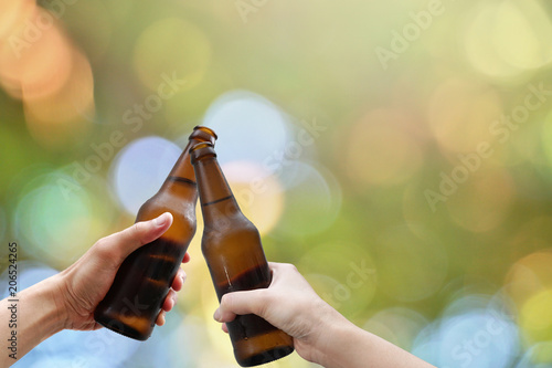 Fotografía  Hands holding two beer bottle and happy enjoying harvest time together to clinking glasses at outdoor party on beautiful bokeh light background
