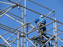 Construction Worker Working On Scaffolding. Steeplejack On The Background Of Clear Blue Sky
