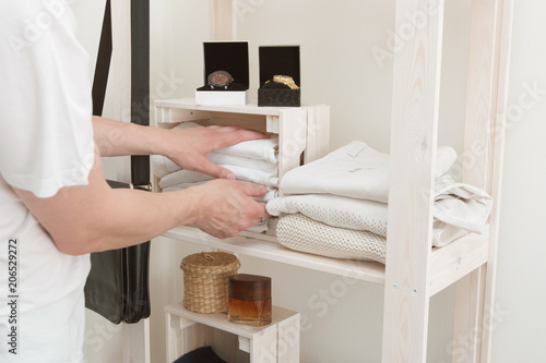 Fotografia, Obraz  Young handsome European man with dark hair brings wardrobe order puts everything on its place hides things in boxes