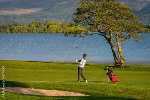 Lone golfer playing golf at golf course with picturesque