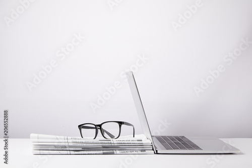 Fotografia  laptop and eyeglasses on heap of newspapers, on white