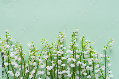 In de dag Lelietje van dalen Romantic gentle flower background, lily of the valley on a mint color background, top view, flat layout.