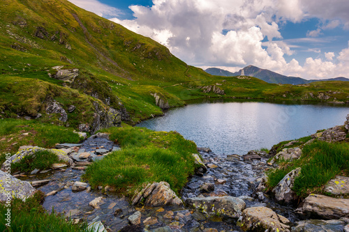 Aluminium Prints New Zealand rapid streams flow to lake Capra in mountains. Fagaras mountain ridge under the gorgeous cloudscape in the distance. Beautiful summer landscape of Romania
