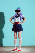 Full Length View Of Girl In Bright Wig Using Virtual Reality Headset And Standing With Hands On Waist On Blue