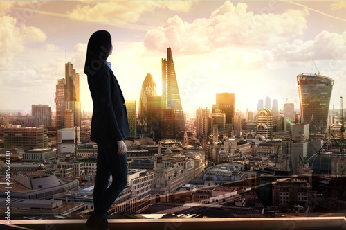 Fototapeta Young woman in suit looking over the City of London at sunrise  obraz na płótnie