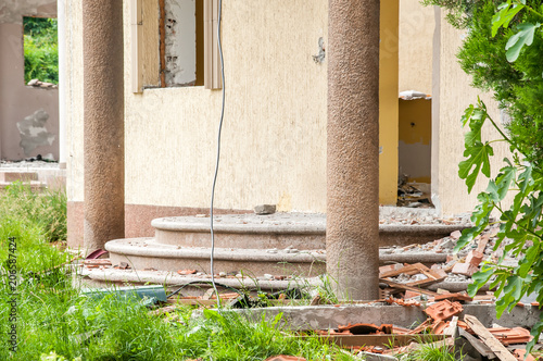 Foto op Aluminium Op straat Damaged stairs and wall of domestic civilian villa house or building with hole without windows and doors destroyed by grenade in the war zone