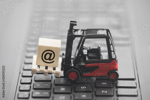 Forklift with email symbol on wooden block over laptop keyboard
