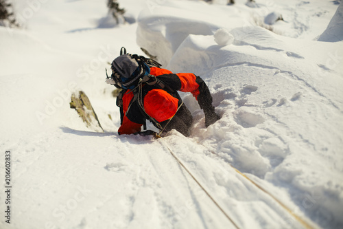 Fotografie, Obraz  Mountaineer overcomes the complicated section on a snow-covered mountain slope