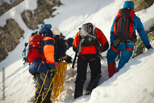 Photo sur Aluminium Alpinisme Group climbers on a snowy mountain slope.