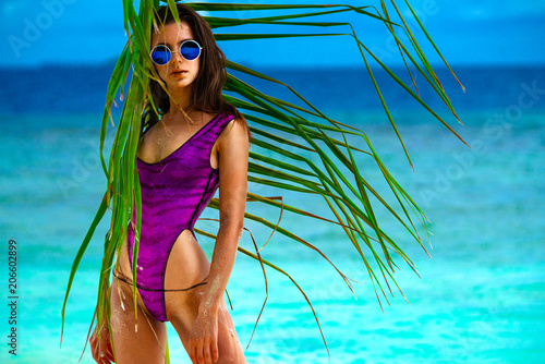 Obraz Model in a raspberry swimsuit with palm branch on the beach - fototapety do salonu