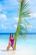 Girl swimsuit with palm branch on background of ocean