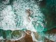 Aerial view of ocean waves and brown rocks in the coastline