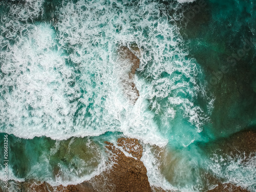 Photo Stands Air photo Aerial view of ocean waves and brown rocks in the coastline