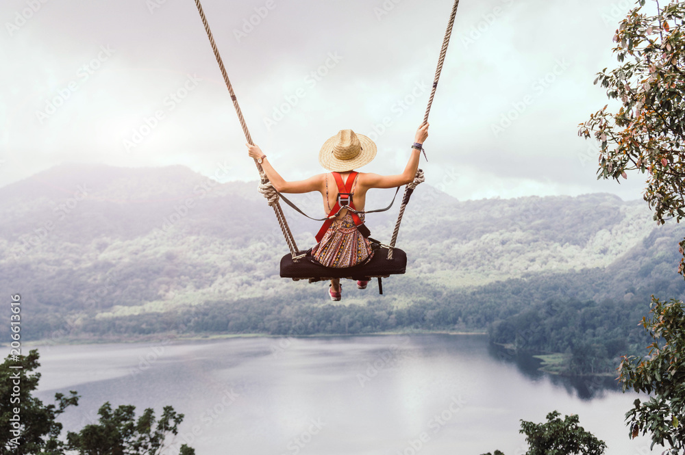 Fototapeta Carefree woman on the swing on a inspiring landscape.