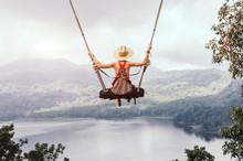 Carefree Woman On The Swing On A Inspiring Landscape.