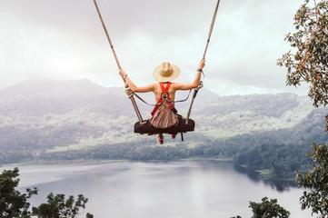 Beztroska kobieta na huśtawce na inspirującym krajobrazie.