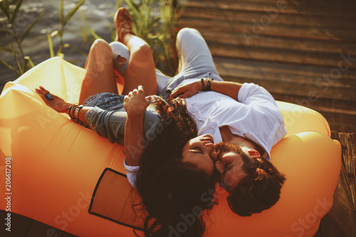 Obraz Young couple lying in a lazy bag during the sunset - fototapety do salonu