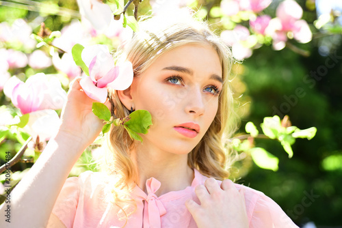 0ee258bb01bf7 Pretty girl in pink blouse posing next to flowering tree. Blond young woman  holding tender