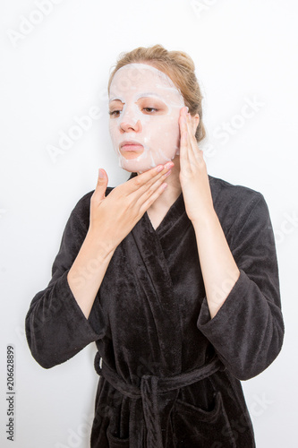 Fotografie, Tablou  blond woman putting a make-up mask on her face