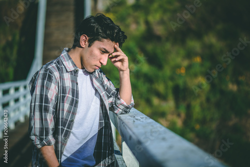 Sad depressed and desperate young male standing on a bridge contemplating suicid Canvas-taulu