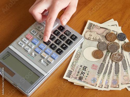 Fotografiet 計算機でお金の計算をする女性