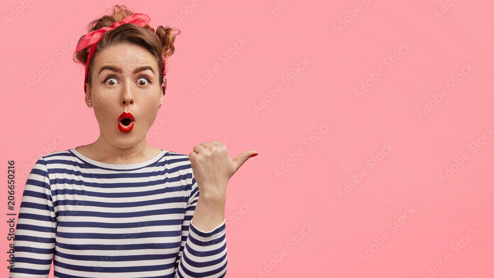 Fototapety, obrazy: Horizontal portrait of beautiful surprised female with attractive look and shocked expression, dressed in retro style, shows something with thumb on blank pink wall. Look at this strange thing