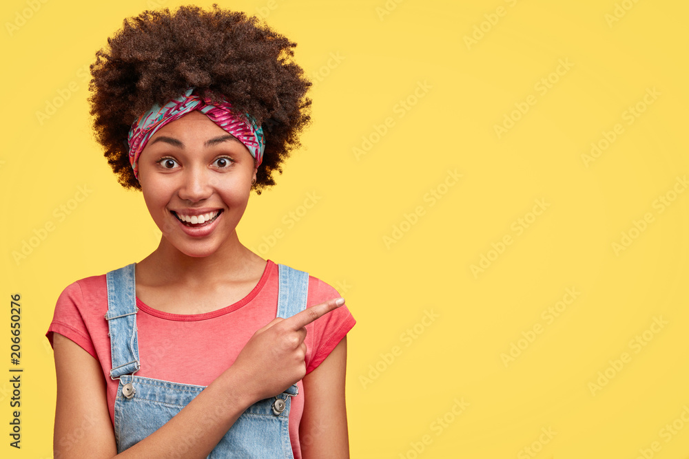 Fototapeta Portrait of delighted African American female, has curly dark hair, dressed in casual clothes, indicates at blank yellow wall as demonstrates announcement, smiles happily at camera. Advertisement