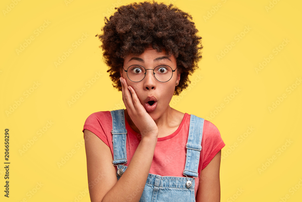 Fototapeta Photo of attractive young female with amazed look, keeps hand on cheek, feels puzzled and surprised as notices something unexpected, has Afro hairstyle, stands indoor against yellow background - obraz na płótnie