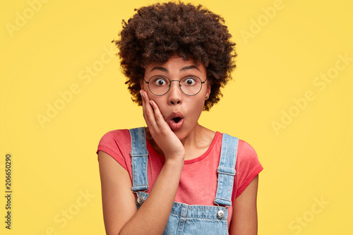 Fototapeta Photo of attractive young female with amazed look, keeps hand on cheek, feels puzzled and surprised as notices something unexpected, has Afro hairstyle, stands indoor against yellow background obraz na płótnie